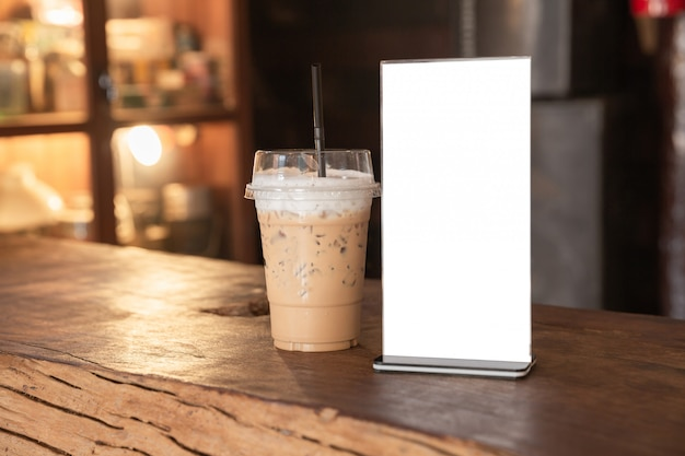 コーヒーショップの木のテーブルの上にメニューフレーム立っています。テキストマーケティングプロモーションのためのスペース