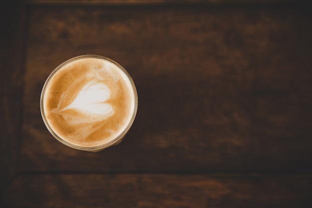 コーヒーショップカフェの木のテーブルにコーヒーのラテカップ