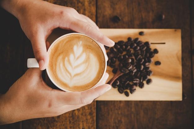 ウッドテクスチャ上の女性の手に一杯のコーヒー。