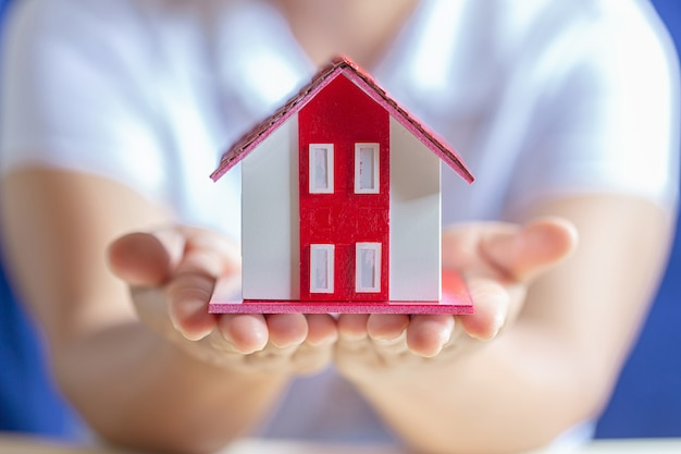 夢の家のモデルを保持している人間の手