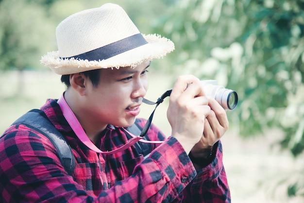 旅行の自然の中でカメラを使用してハンサムな男