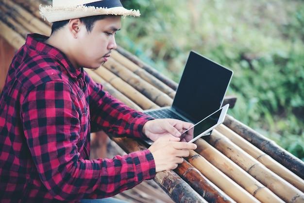 旅行自然の中でラップトップを使用してハンサムな男