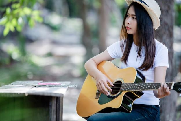 自然で書くとギターを弾く美しい少女の肖像画