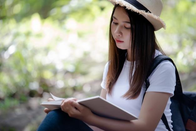 美しい女性が自然に本を読んで