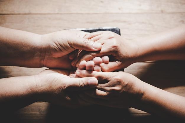 夫と妻のカップルが手を繋いでいるとあなたのテキストのコピースペースを持つ木製のテーブルで一緒に祈る