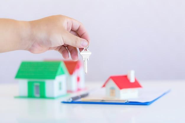 家のモデルとキーを持つ不動産エージェント