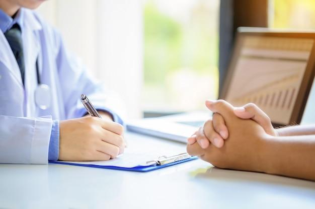 医師の男性が病院の机で申請書を記入しながら患者に相談します。