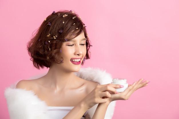 美しさの概念。女性は彼女の手で保湿剤を保持しています
