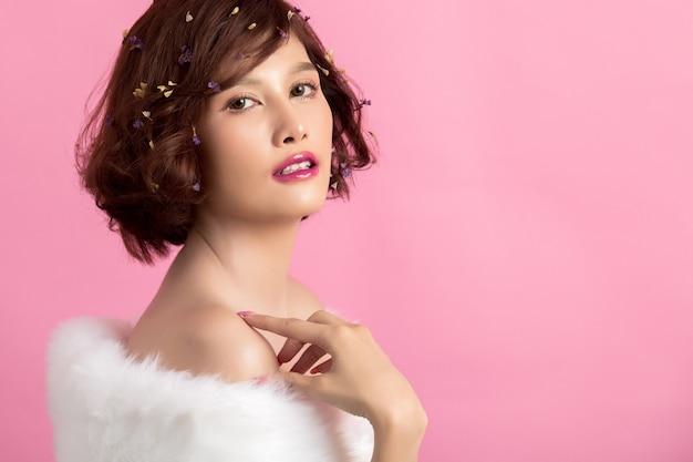 ピンクに分離された美しいアジアの女性