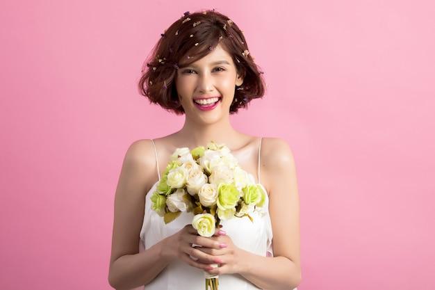 ピンクに分離された花を持って笑顔の遊び心のあるかわいい女の肖像