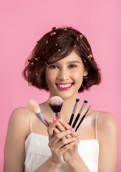 ショートヘアアジアの若い美しい女性の化粧品パウダーブラシを適用する