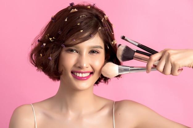 Женщина коротких волос азиатская молодая красивая прикладывая косметическую щетку порошка