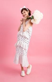 Портрет улыбающегося игривая милая женщина с цветами, изолированных на розовый