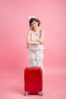 ピンクに分離された旅行スーツケースと夏のカジュアルな服装で旅行者観光客の女性