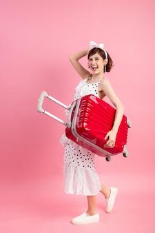 Путешественник туристическая женщина в летней повседневной одежде с чемоданом путешествия, изолированных на розовый