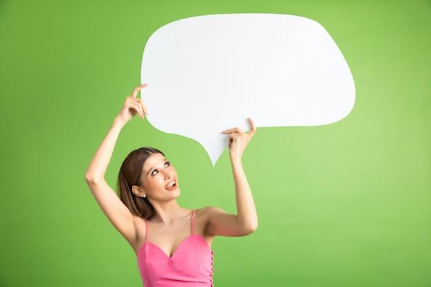 Азиатская женщина держа и смотря вверх к пузырю речи с пустым космосом для текста на зеленом цвете
