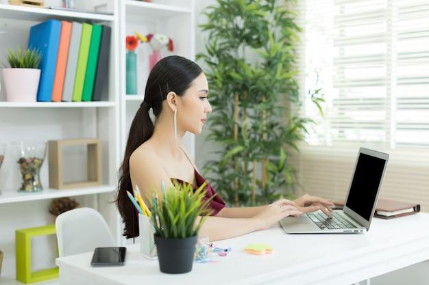 陽気なビジネス女性のオフィスでラップトップに取り組んで