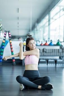 アジアの女性はジムでフィットネスをプレイします。