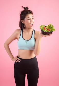 若い女性はピンクの野菜を食べるのが好きです。