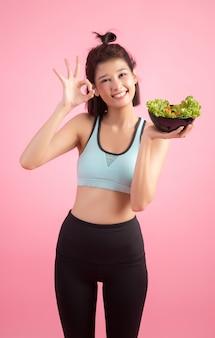 Молодые женщины любят есть овощи на розовом.