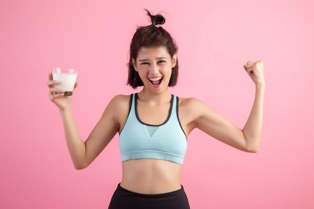 Красивая спортивная женщина пьет молоко