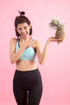 体重を制御する運動の後健康的でうれしそうな笑みを浮かべてパイナップルフルーツ女性
