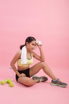 若い美しいフィット女性運動後の水を飲む