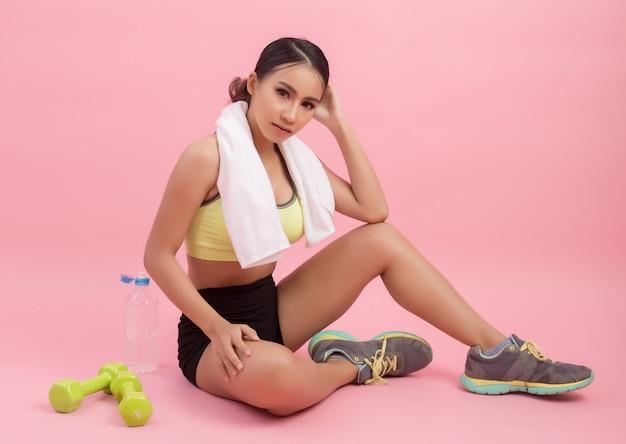 Молодая красивая подходящая питьевая вода женщины после тренировки