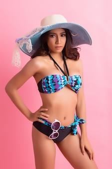 ピンクで分離された水着の若い女性