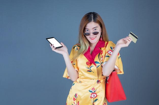 スマートカードや携帯電話を保持している女性