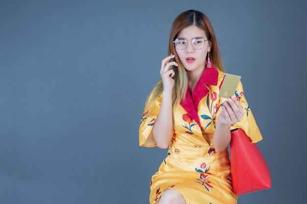 Женщины держат в руках смарт-карты и мобильные телефоны