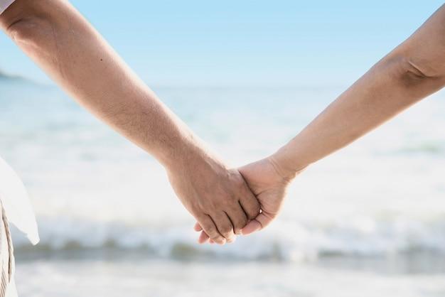 アジアカップルは海の近くに手を握っています。