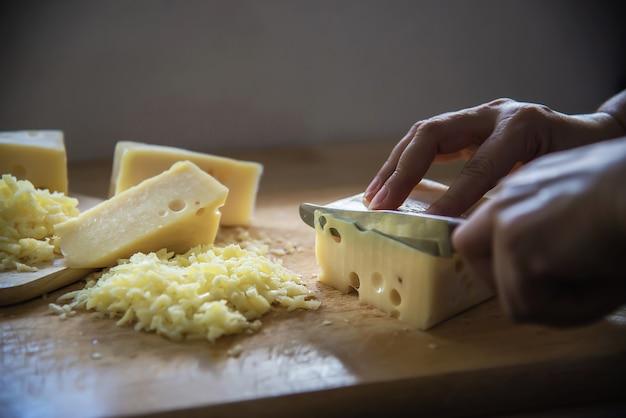 Женщина нарезала ломтик сыра для повара с помощью ножа на кухне - люди делают еду с концепцией сыра