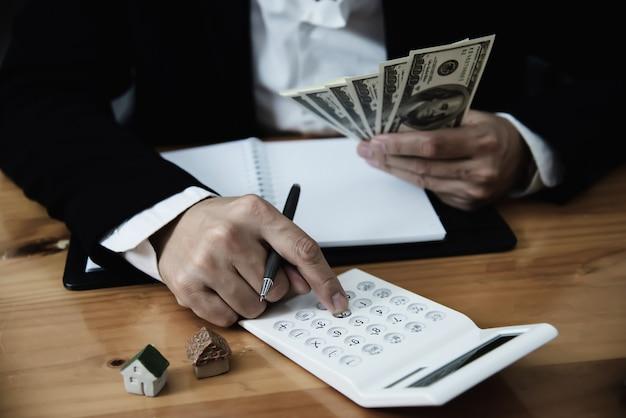 Деловой человек показать деньги банкнота сделать финансовый план пригласить людей, чтобы продать или купить дом и автомобиль