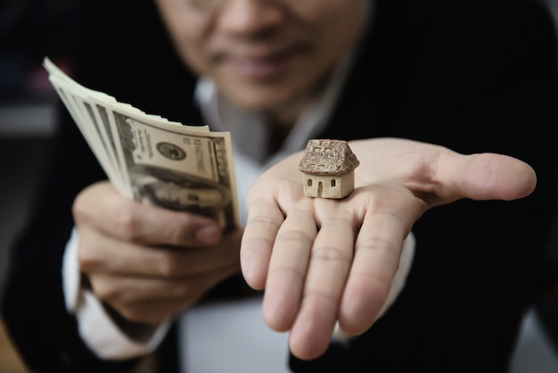 ビジネスマンショーお金紙幣ノート財務計画に家や車 - 金融資産ローン信用保険の概念を売買するように誘う