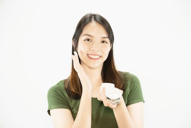 保湿クリームを使用したフェイススキンケア - 女性と化粧品のメイクアップフェイスビューティースキンケアコンセプトの若い美しい女性
