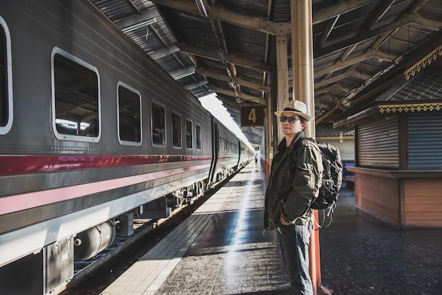 旅行男はプラットフォーム - 鉄道駅交通概念で人々休暇ライフスタイル活動で電車を待つ