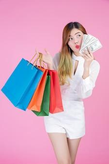 女の子はファッションの買い物袋を保持し、ドルカードを保持しています