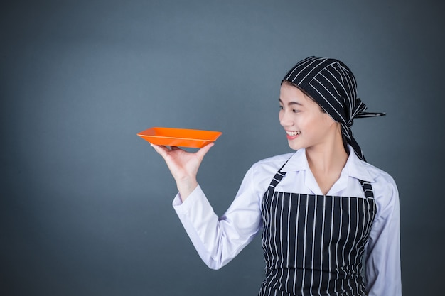 食物と一緒に空の皿を保持している主婦