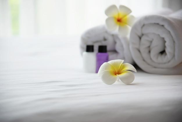 ホテルのタオル、シャンプー、石鹸のバスボトルセットプルメリアの花が飾られた白いベッドの上 - ホテルリゾートコンセプトでリラックスした休暇
