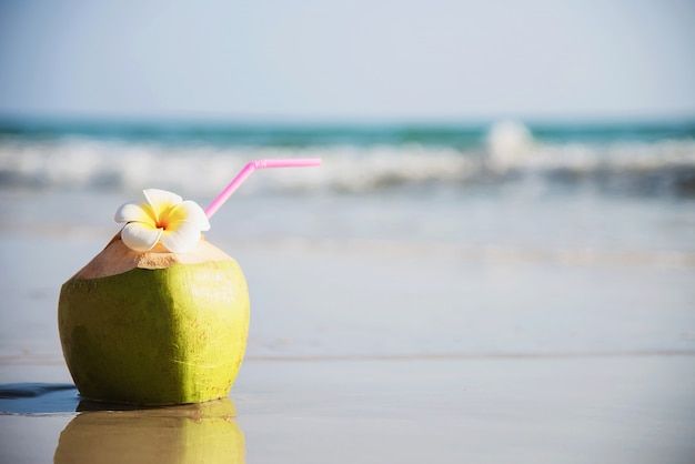 Свежий кокос с цветком плюмерии, украшенный на чистом песчаном пляже с морской волной - свежие фрукты с концепцией отдыха на солнце с морским песком