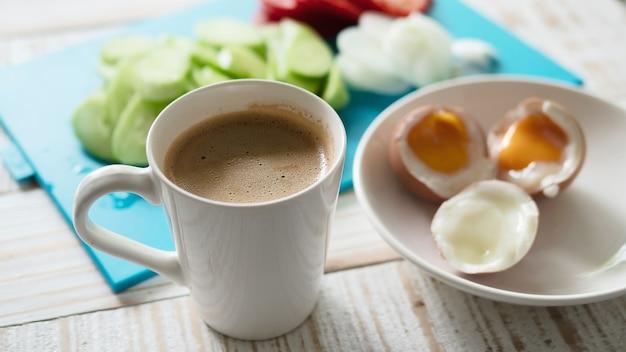 ゆで卵、新鮮なキュウリのサラダとコーヒーカップの朝食セット - トップビュー朝食食品のコンセプト
