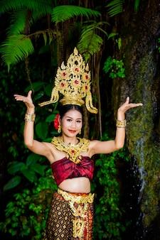 女性は滝に古代のタイのドレスを着ていました。