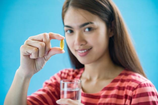 医師の指示の後の薬を飲んで若い女性