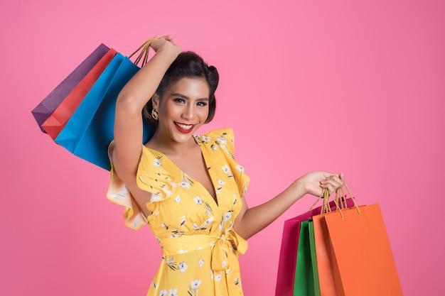 Красивая азиатская женщина держа покрашенные хозяйственные сумки