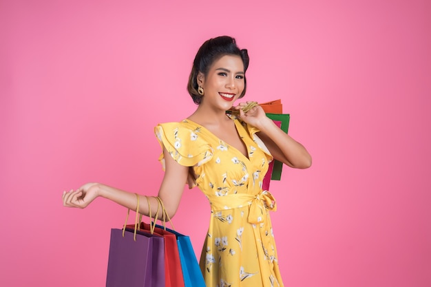 色の買い物袋を保持している美しいアジアの女性