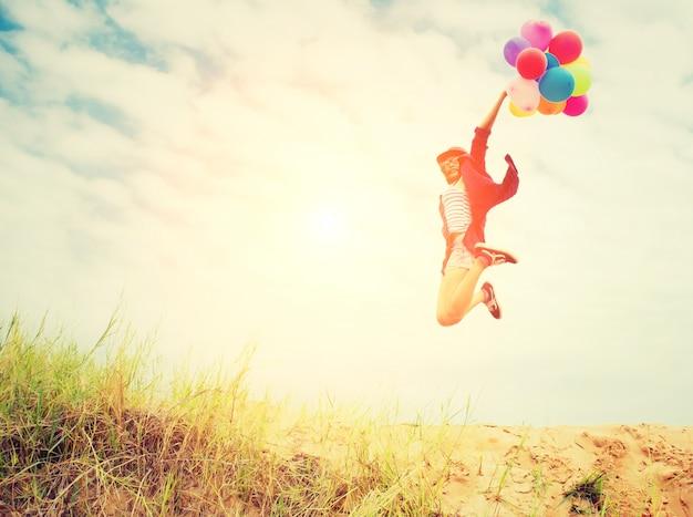 風船とビーチでジャンプガール