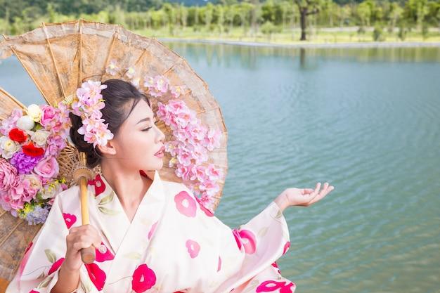 Красивая азиатская женщина нося японское кимоно, традиционную концепцию платья.