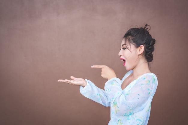 Девушка показывает жесты рук и эмоции лица.