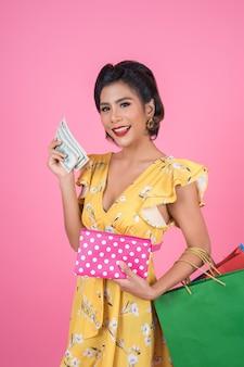Молодая женщина моды, держащая бумажник и хозяйственные сумки